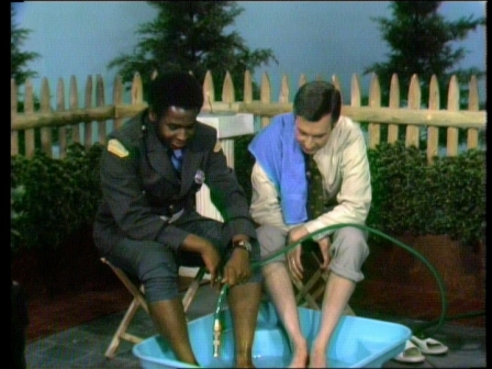 Officer Clemmons and Mr. Rogers share a hose in a pool